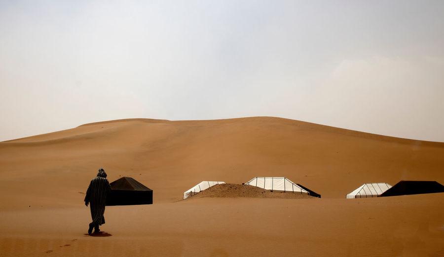 Rear view of man standing on desert against sky