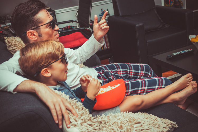 Togetherness Lifestyles Men Watching Watching Tv Watching A Movie 3D 3D Glasses  Eyeglasses  Eyewear Home Interior Living Room Adult Child Offspring Father Parent Family Fun Enjoyment Parenthood Father And Son Kid Relaxation Weekend Caucasian People Two People Bonding Sofa Son Childhood Males  Real People Leisure Activity Positive Emotion Casual Clothing
