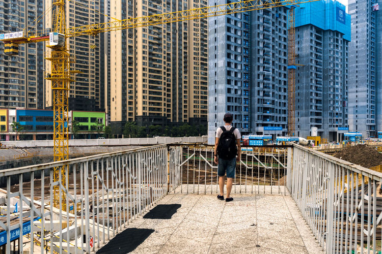Adult Architecture Bridge Bridge - Man Made Structure Building Building Exterior Built Structure City City Life Connection Day Full Length Hairstyle Nature Office Building Exterior One Person Outdoors Railing Skyscraper Standing Walking Women Young Adult