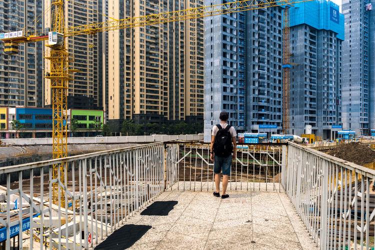 Woman Walking On Bridge Against Buildings In City