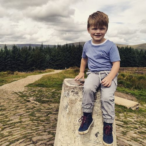 Portrait of sitting on built structure at beacon fell against sky