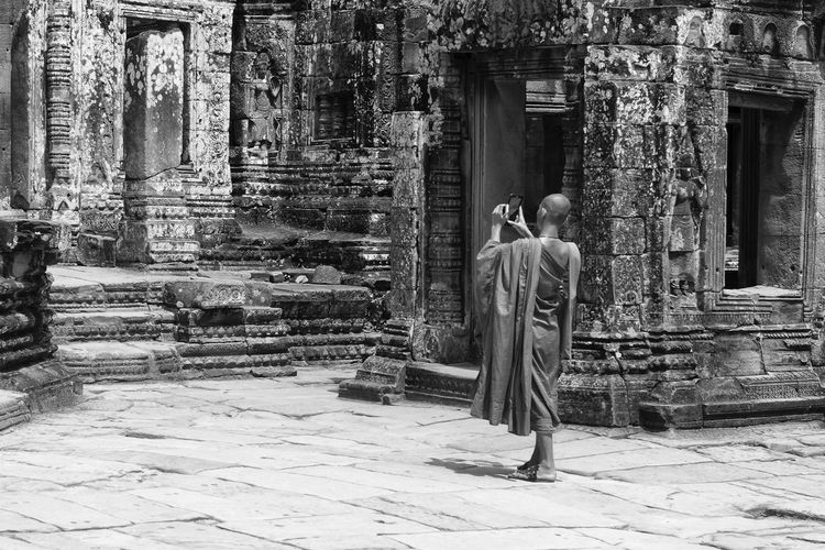 Young Monk Taking Pictures History Spirituality Religion Rear View Buddhism Buddhist Monk Bw Black And White Angkor Wat Siem Reap ASIA Young Monk  Buddhist Taking Pictures Mobile Phone UNESCO World Heritage Site Ruins Travel Destinations Travel Holiday Vacations Landmark Lifestyles Tourism