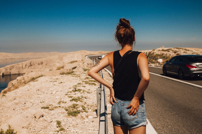 Rear view of woman standing on street against sky