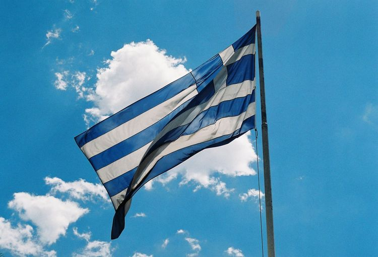 Low angle view of greek flag against blue sky