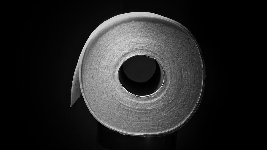 Close-up of rolled toilet paper against black background