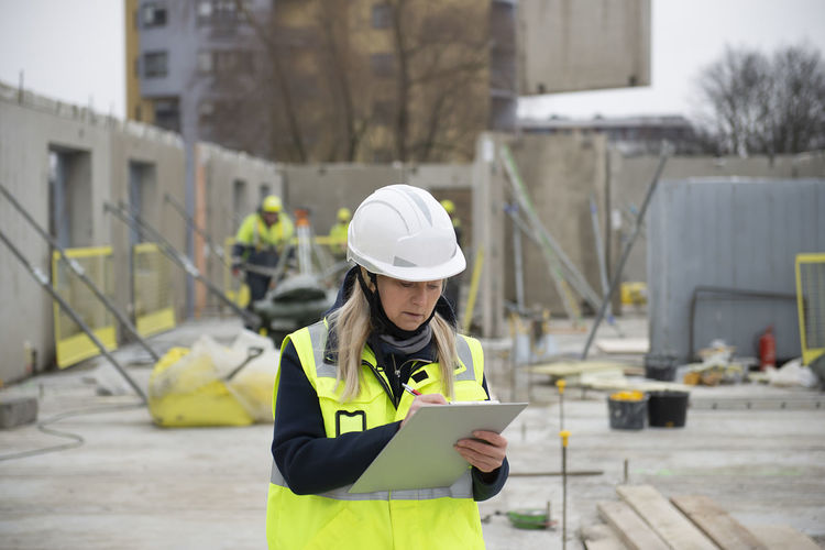 Woman construction site engineer architect worker with hard hat writes notes on the progress of work