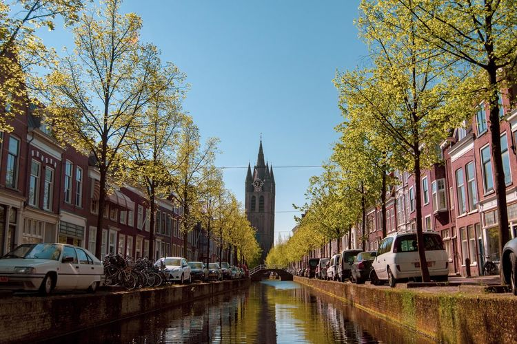 Oude Kerk Building Exterior Architecture Plant Day Religion Tower Built Structure Building Sky Tree Outdoors Nature Mode Of Transportation Car Motor Vehicle Transportation Place Of Worship Land Vehicle No People Row House Residential District Street City Canal