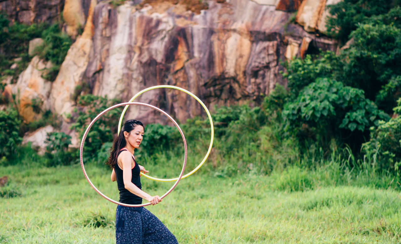 Side view of woman spinning hula hoop while walking on grassy field