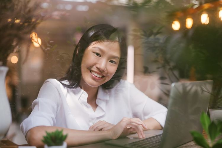 Portrait of happy businesswoman using laptop at table seen through window