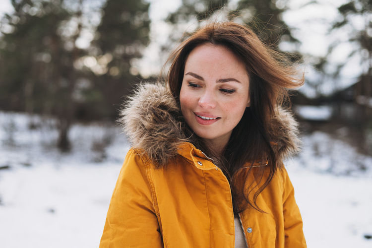 Portrait of young smiling beautiful woman in yellow jacket walking in winter forest