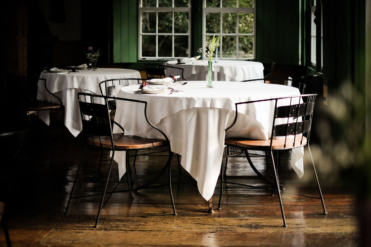 Empty chairs with table at restaurant