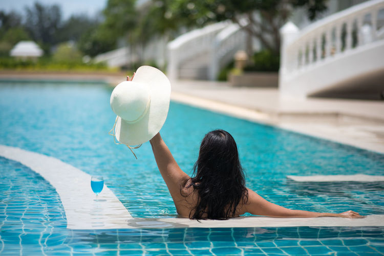 Woman With Drink In Swimming Pool
