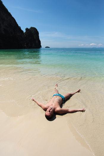 Shirtless man lying at beach against blue sky