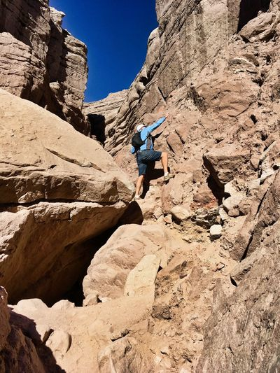 Low Angle View Of Man Climbing On Rock Formation During Sunny Day