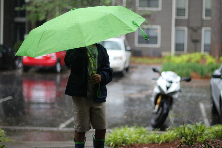 Midsection Of Boy With Umbrella Standing On Street During Rainfall
