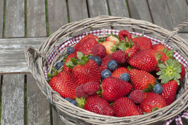 Close-Up Of Various Berry Fruits In Wicket Basket On Table