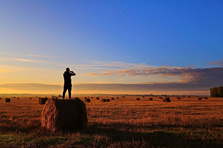 Man standing on hay bale at farm against sky during sunset