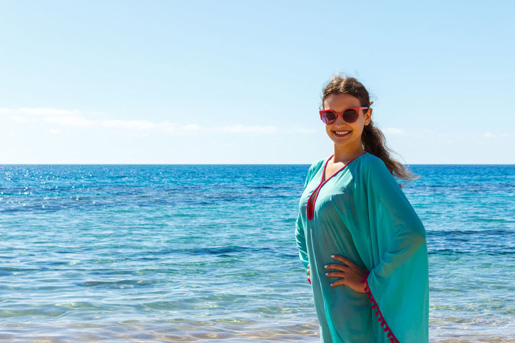 Portrait of smiling young woman standing at beach against sky during summer