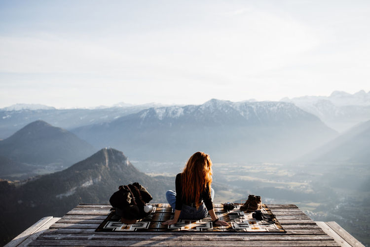 Rear view of women sitting on mountain against sky