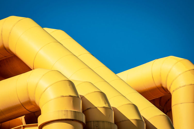 Low angle view of yellow pipes against clear blue sky