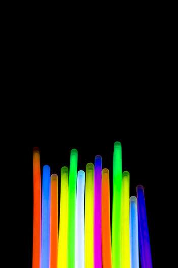 Close-up of colorful illuminated glow sticks against black background