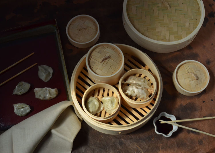 pot stickers in Dim Sum steamer. In Hong Kong, China, Dim Sum restaurants are packed with people who eat Dim Sum for breakfast. In the USA we eat Dim Sum later in the day. Bamboo Chinese Food Chopsticks Containers Cooked Dim Sum Fresh Group Of Objects Lids No People Ready-to-eat Soy Sauce Steamed  Steamed Dumplings Steamer Tray