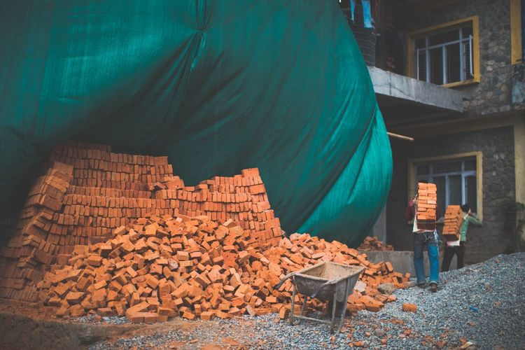 Workers working by bricks at construction site