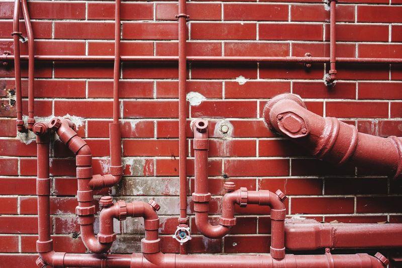 Fire hydrant against brick wall