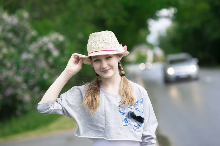 Romantic beautiful girl wearing a summer straw hat smiles on the street,car lights in the background
