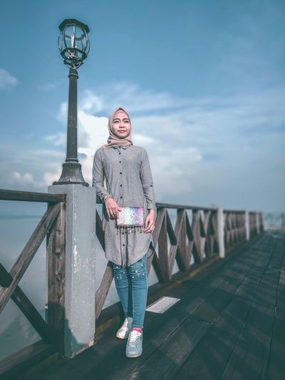 Portrait of woman standing on railing against sky