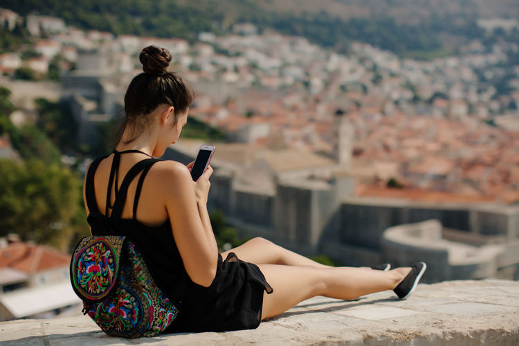 Woman Using Mobile Phone On Wall