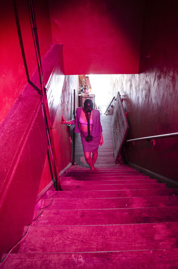 High angle view of woman with gas mask walking on illuminated steps in building