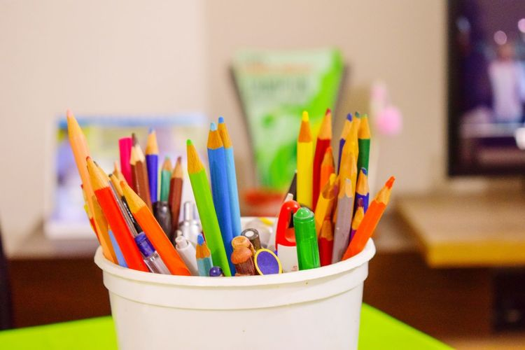 Close-up of colored pencils in container on table