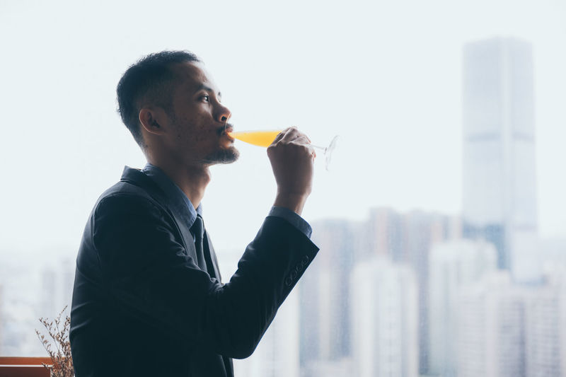 Young man drinking glass against cityscape