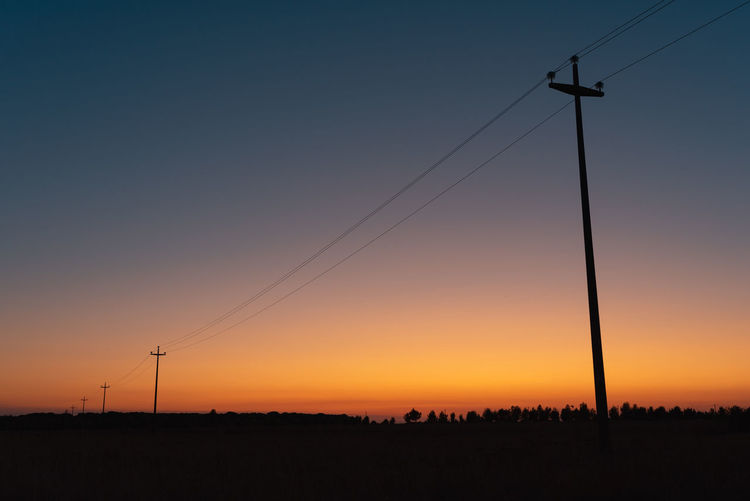 Scenic view of silhouette field against clear sky during sunset