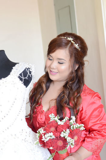Smiling young woman looking at wedding dress against white wall at home