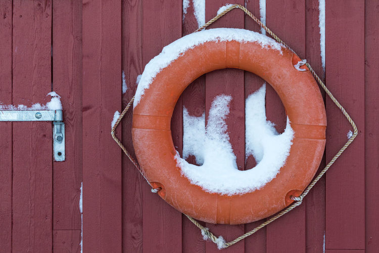 Snow On Life Belt Hanging From Wooden Wall