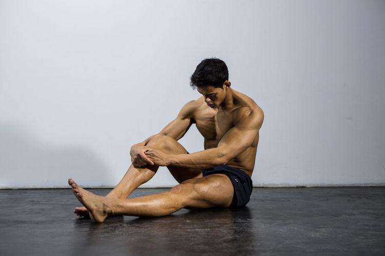 Shirtless Muscular Man Sitting Against Wall