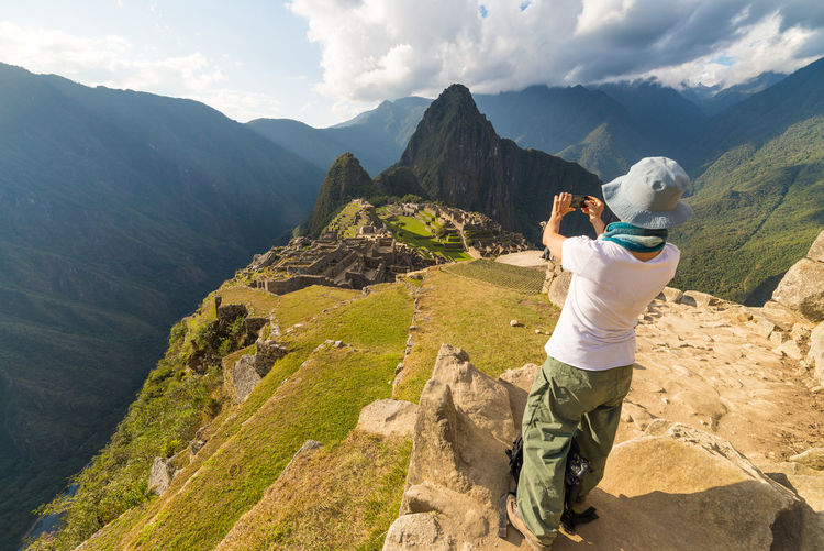 Rear view full length of woman photographing machu picchu