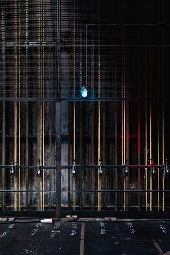 Padlocks hanging on building gate at night