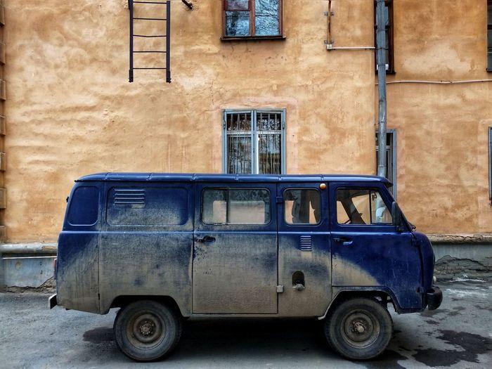 Old vintage car on street against building