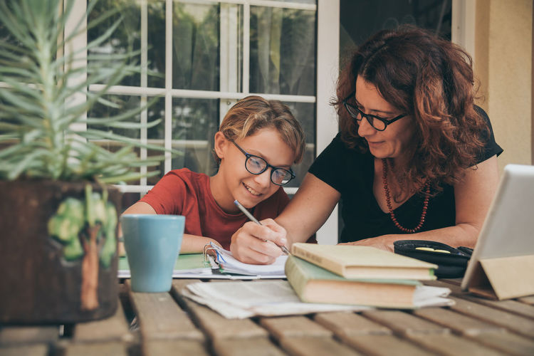 Mother assisting son in homework at home