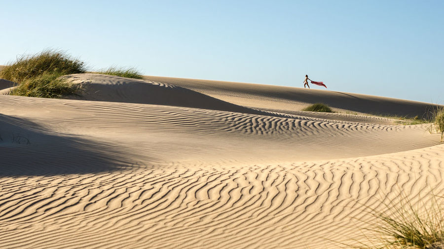 Distant view of woman walking on desert