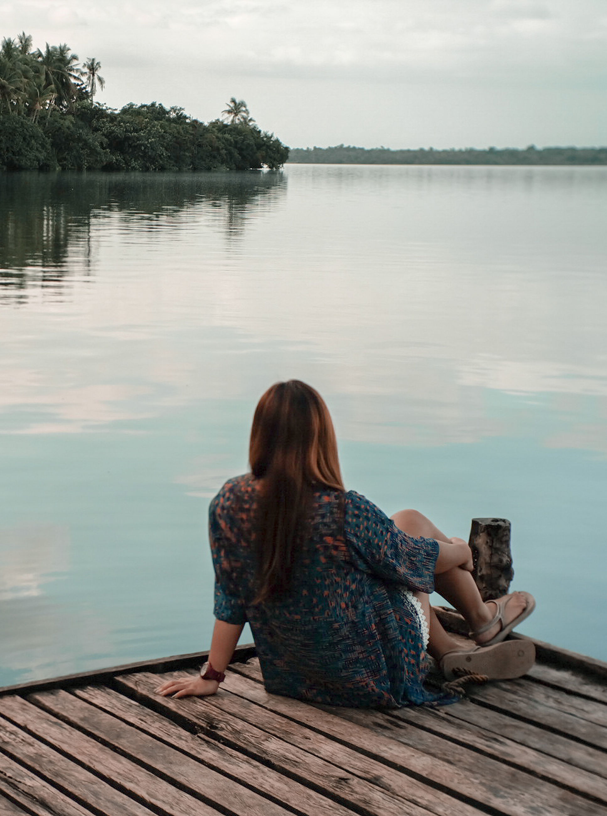 water, rear view, leisure activity, real people, one person, lake, pier, nature, beauty in nature, sitting, jetty, tranquil scene, full length, tranquility, lifestyles, scenics, outdoors, day, wood - material, relaxation, women, sky, young women, wood paneling, tree, young adult