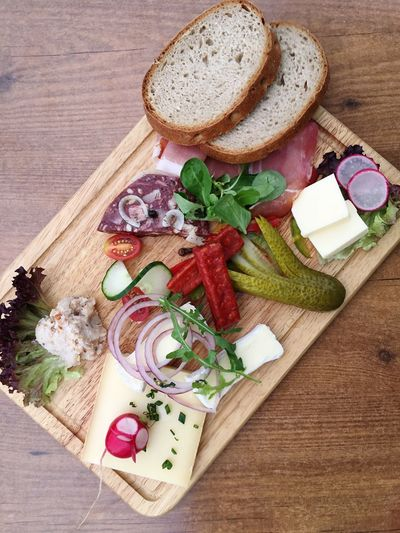 High Angle View Of Bread And Vegetables On Wooden Table