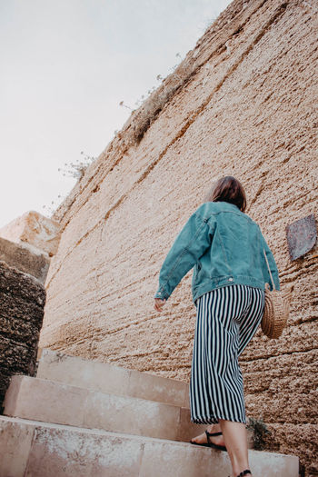 Rear view of woman walking against wall
