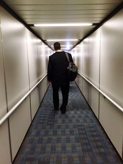Rear view of businessman walking in passenger boarding bridge with backpack