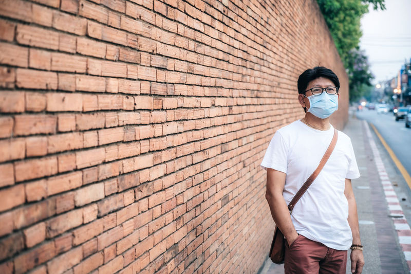 Man wearing mask standing against brick wall