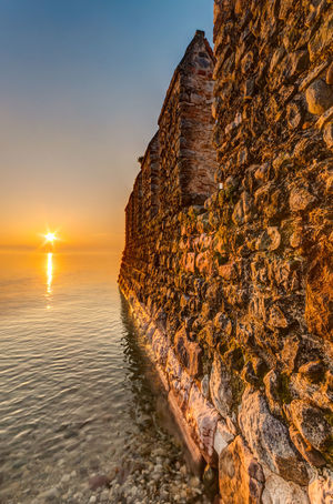 Sunrise by the Castle. Architecture Battlements Calm Castle Clear Sky Horizon Over Water Landscape Mist No People Outdoors Pebbles Quiet Rays Reflection Ripples Scenics Sirmione Sky Sun Sunlight Tranquility Wall Water