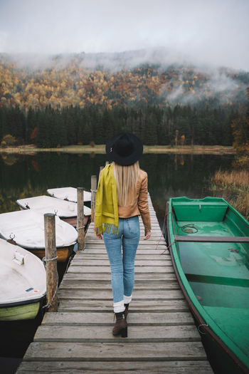 Rear view of woman standing on boat in lake